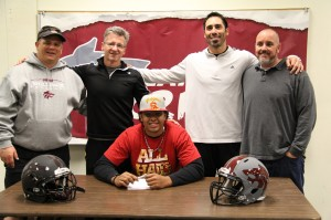 CHS football coaches (from left to right) Terrance Lynch, Mike Collins, Ryan Campuzano, and Shane Hile stand behind graduated senior Jordan Austin (center). Austin signed to USC on Dec. 19 in the health room at CHS and has already started his football career at USC.