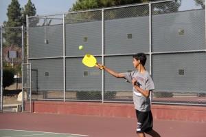 Freshman Jesse De La O swings his racquet in an attempt to hit the wiffleball in a pickleball match.
