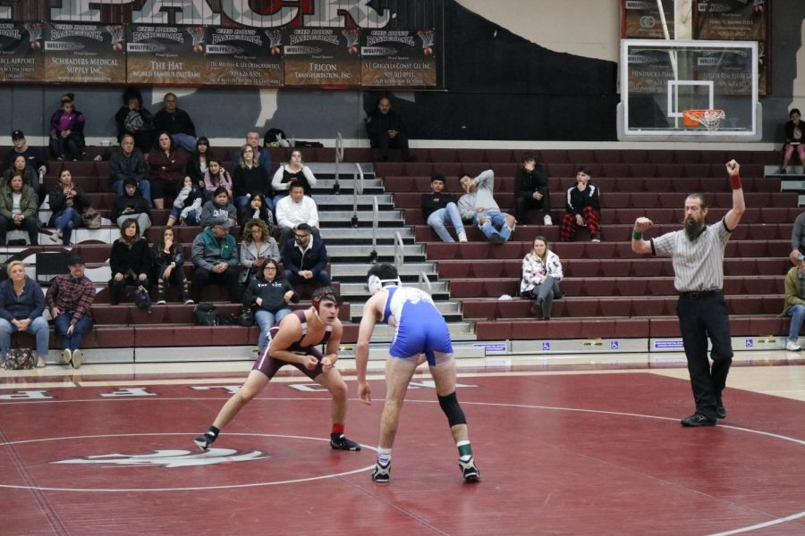 Athletes wrestle in the CHS gym. In stark contrast with  the fall football games attended by hundreds of community members, the stands are largely empty. Had more people shown their support, the atmosphere in the gym could have had a positive effect on athletes' performance.