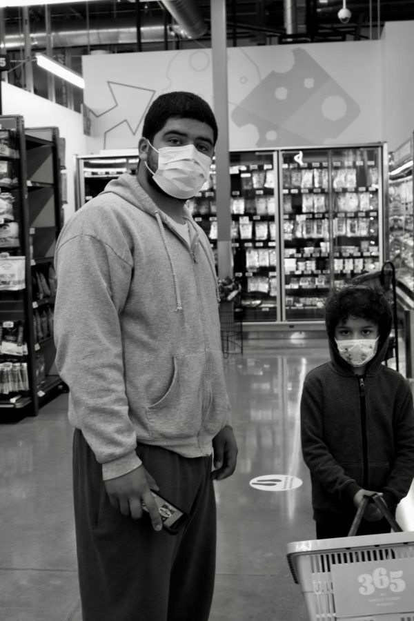 A father and his young son wait for groceries to be restocked at Whole Foods
