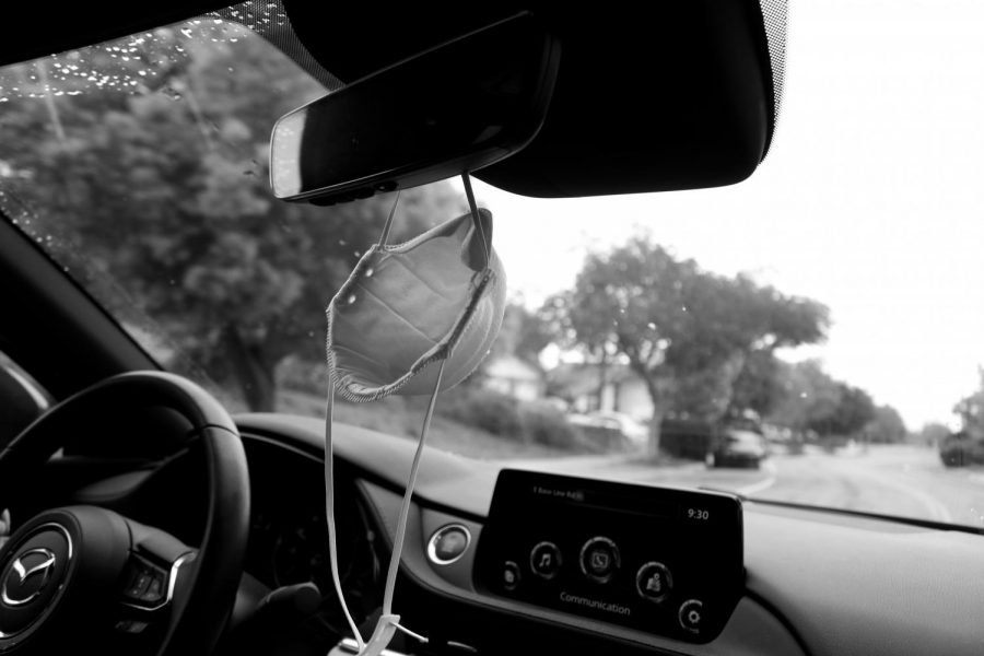 An expired N-95 mask dangles from the rear-view mirror of a car