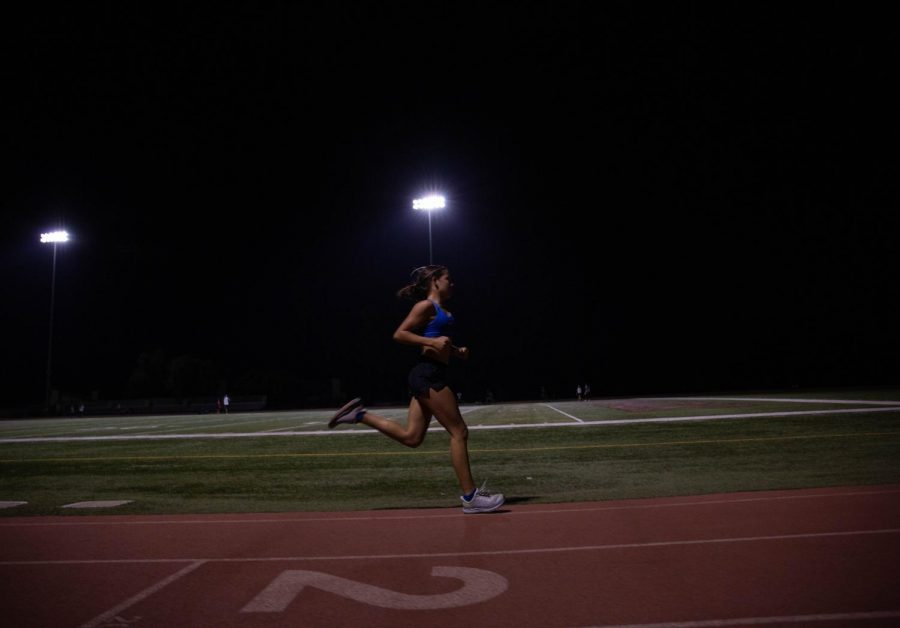 Junior Maddie Coles races the 3200 under the stadium lights on Friday, October 16.