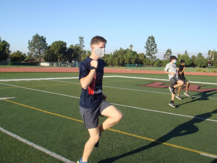 Junior Ryan Hinson completes a pre-run drill routine with other cross-country runners on Saturday.