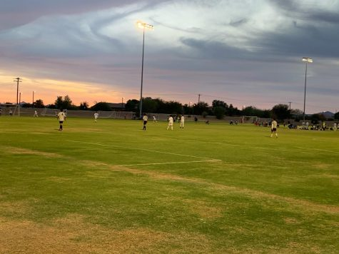 A soccer game takes place at dusk in Arizona, where club sports are permitted to compete.