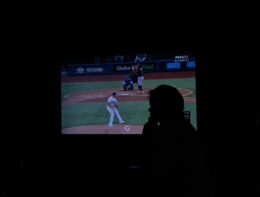 The silhouette of a sports fan watches a baseball game from home, yet the