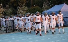The team walks onto the field at an away game.
